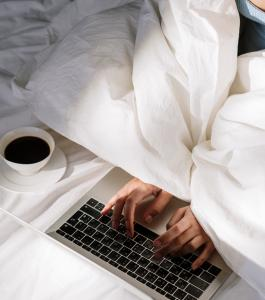 Working on a laptop computer while hiding under the sheets of a bed
